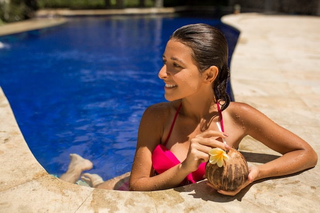 Giovane femmina castana esile sexy che posa con la noce di cocco fresca in stagno con acqua blu di cristallo