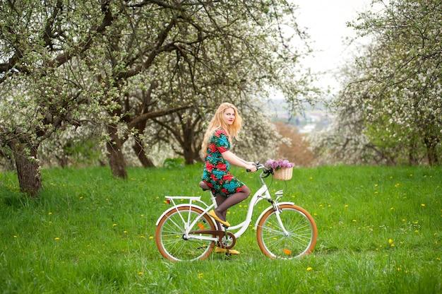 Giovane femmina che guida una bicicletta bianca d'annata con la merce nel carrello dei fiori