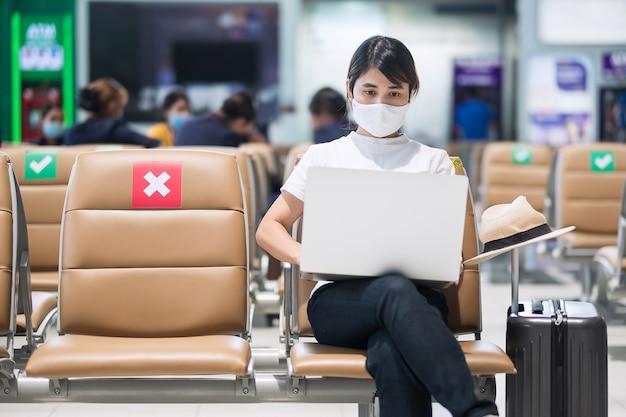 Giovane femmina che indossa la maschera per il viso e utilizza il laptop del computer in aeroporto, protezione dall'infezione da malattia di coronavirus, viaggiatore asiatico della donna che si siede sulla sedia. new normal, social distancing e digital nomad