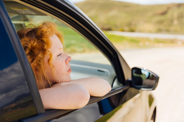Giovane femmina che osserva dalla finestra di automobile