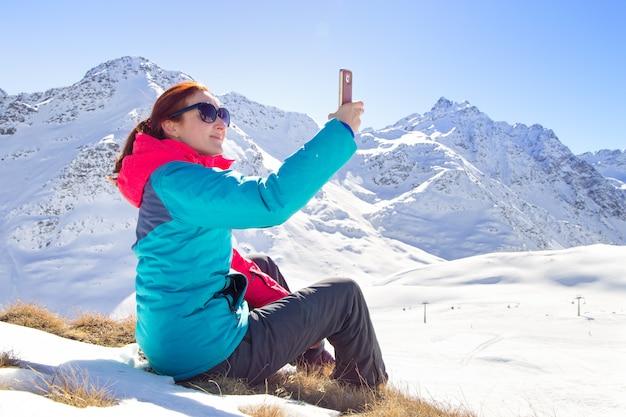 Giovane femmina che prende un selfie sul suo telefono su una bella cima della montagna. orario invernale