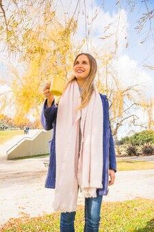 Giovane femmina che sta con la tazza di tè nel parco di autunno