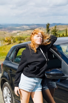 Giovane femmina che sta vicino all'automobile nera