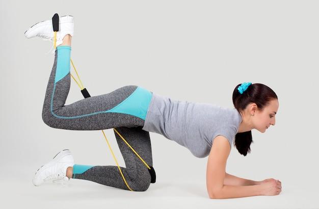 Giovane femmina con espansore di fitness in stretching