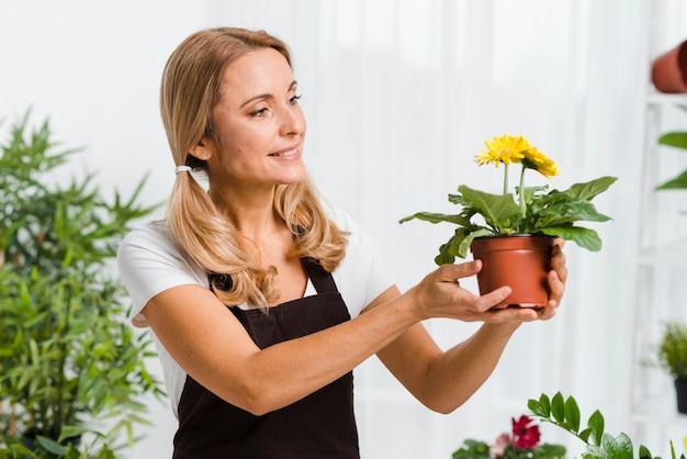 Giovane femmina con i fiori premurosi del grembiule