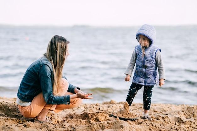 Giovane femmina con il suo castello della costruzione del bambino in sabbia sulla spiaggia vicino al mare. genitore con ritratto divertente stile di vita del bambino. maternità e infanzia. famiglia felice all'aperto.