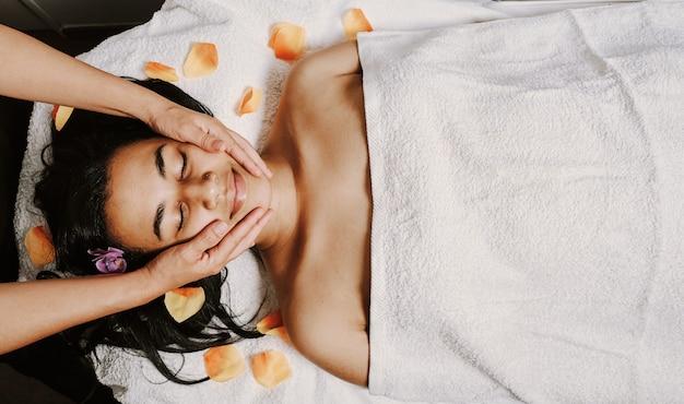 Giovane femmina dell'afroamericano che ottiene un massaggio facciale e capo