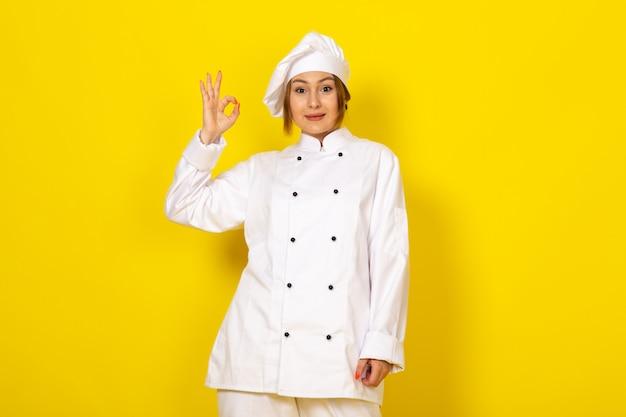 Giovane femmina di cottura in abito bianco cuoco e berretto bianco sorridente segno va bene