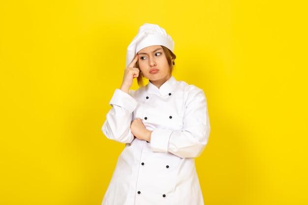 Giovane femmina di cucina in abito bianco cuoco e berretto bianco espressione di pensiero