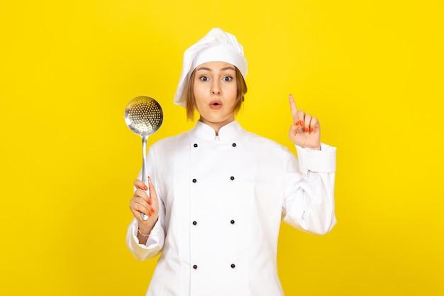 Giovane femmina di cucina in abito bianco cuoco e berretto bianco in posa pensando tenendo cucchiaio d'argento con un'idea