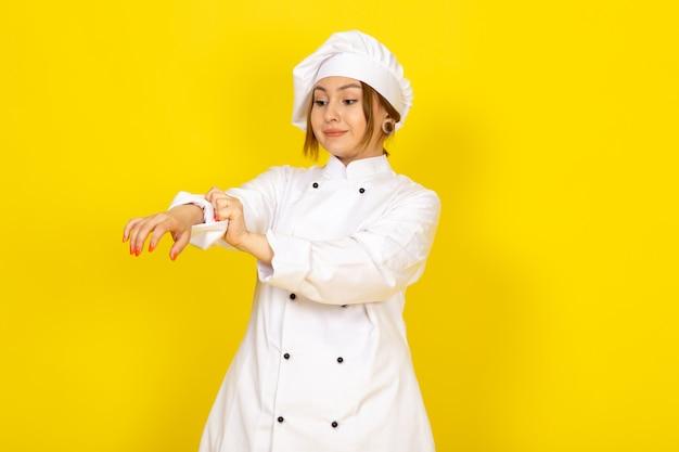 Giovane femmina di cucina in abito bianco cuoco e berretto bianco sorridente che fissa il suo vestito