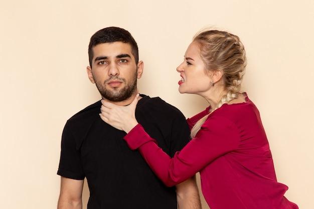 Giovane femmina di vista frontale in camicia rossa che soffoca maschio sulla violenza del modello di emozione della foto dello spazio crema