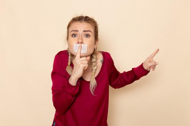 Giovane femmina di vista frontale in camicia rossa con la bocca legata che mostra il segno di silenzio sul panno femminile dello spazio crema