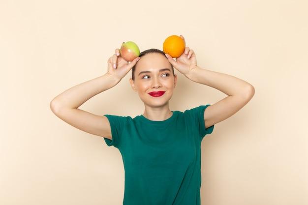 Giovane femmina di vista frontale in camicia verde scuro e blue jeans che tengono mela e arancia con il sorriso sul suo fronte sul beige