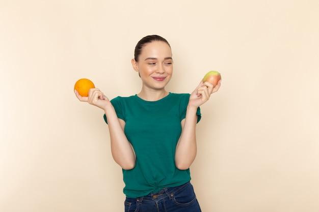Giovane femmina di vista frontale in camicia verde scuro e blue jeans che tengono mela e arancio che sorridono sul beige