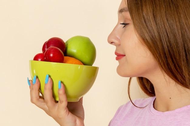 Giovane femmina di vista frontale in maglietta rosa e blue jeans che tengono piatto con la frutta che lo odora