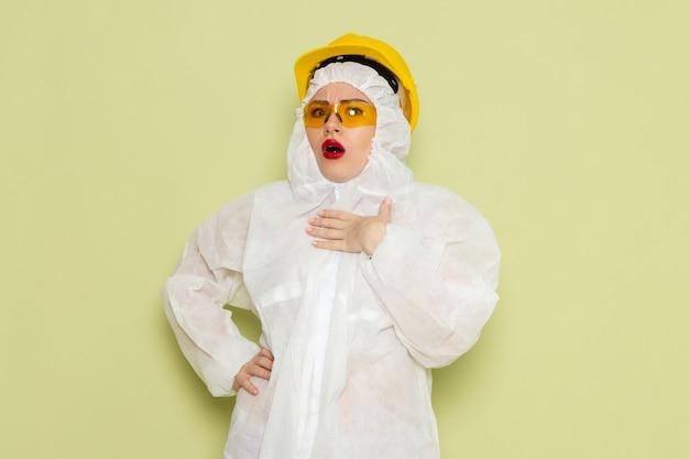 Giovane femmina di vista frontale in vestito speciale bianco e casco giallo che posa con l'espressione confusa sul lavoro dello spazio verde