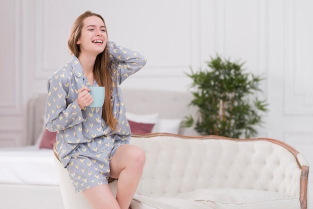 Giovane femmina felice con la tazza di tè a casa