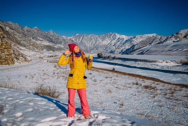 Giovane femmina felice in vestiti luminosi contro le montagne della neve