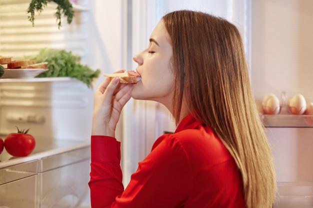Giovane femmina mangia delizioso sandswich con salsiccia, si trova di fronte al frigorifero aperto, tiene gli occhi chiusi con piacere, vestita in camicia rossa