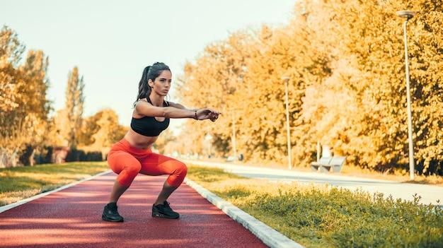 Giovane femmina motivata facendo squat nel parco all'aperto.