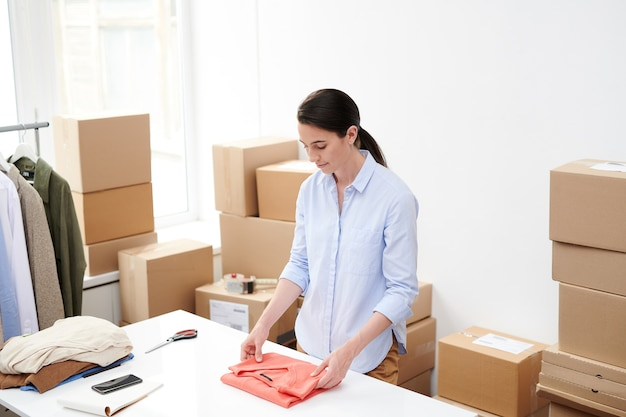 Giovane femmina negozio online lavoratore pieghevole pullover rosso per l'imballaggio mentre in piedi scrivania in ufficio