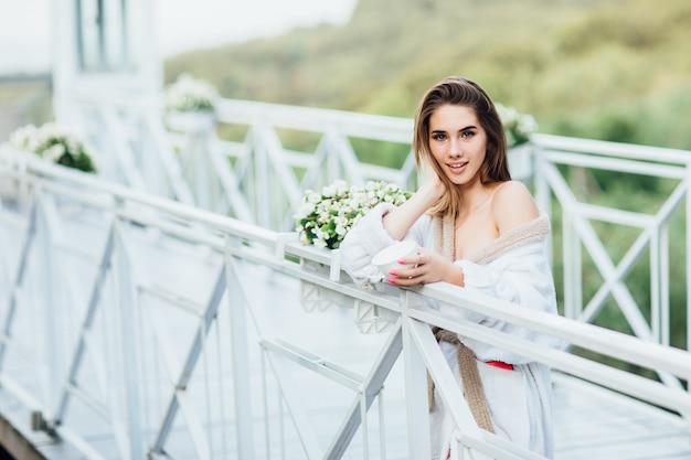 Giovane femmina o sposa sorridente che posa con la tazza di una certa bevanda, indossando all'abito bianco.