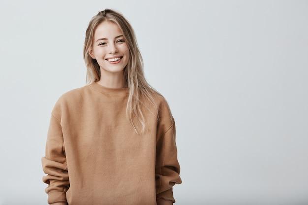 Giovane femmina positivo allegro con capelli biondi, vestito con indifferenza. emozioni e sentimenti positivi
