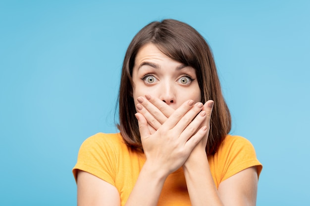 Giovane femmina stupita o scioccata con i capelli scuri che si copre la bocca con le mani mentre ti fissa