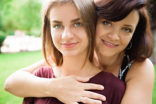 Giovane figlia sveglia che abbraccia sua madre con amore.