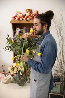Giovane fiorista maschio che sente l'odore dei tulipani gialli nel negozio di fiori
