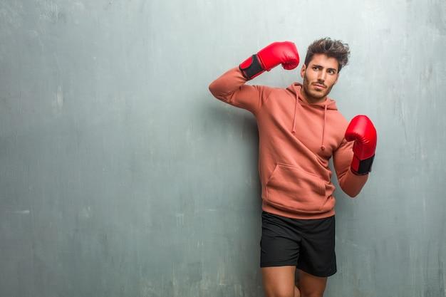 Giovane fitness uomo contro un muro grunge facendo un gesto di suicidio, sentendosi triste e spaventato formando una pistola con le dita.