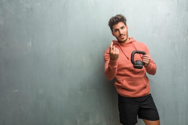 Giovane fitness uomo contro un muro grunge invitando a venire