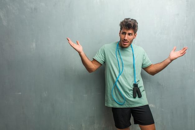 Giovane fitness uomo contro un muro grunge pazzo e disperato, urlando fuori controllo