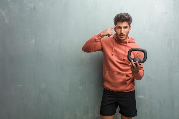 Giovane fitness uomo contro un muro grunge uomo facendo un gesto di concentrazione