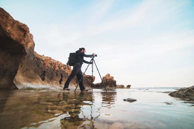 Giovane fotografo alla moda che fa le foto del mare con la macchina fotografica su un treppiede