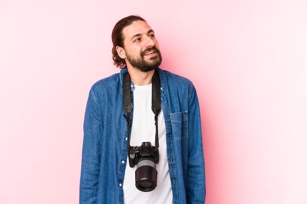 Giovane fotografo caucasico uomo isolato sognando di raggiungere obiettivi e scopi