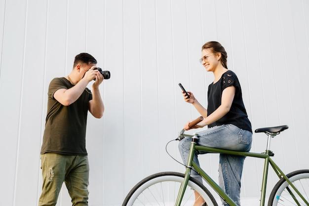 Giovane fotografo che prende foto della donna graziosa alla moda che sta con la bici e che per mezzo di uno smartphone. all'aperto.