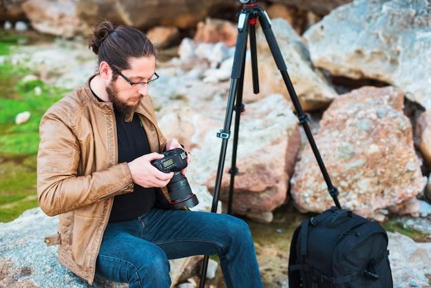 Giovane fotografo elegante seduto su una roccia e guardando le foto che ha fatto sulla sua macchina fotografica