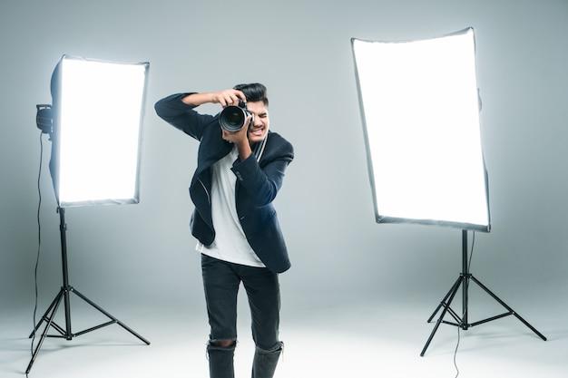 Giovane fotografo indiano professionista che prende le foto in studio con leight