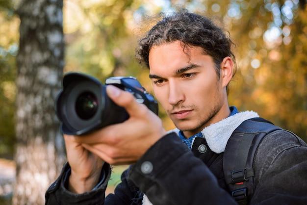 Giovane fotografo maschio che fotografa natura