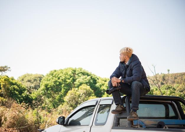 Giovane fotografo seduto sul suo camioncino picking fotografare in montagna.