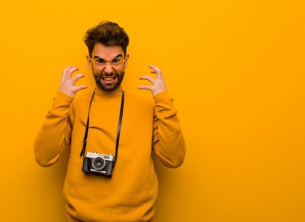 Giovane fotografo uomo arrabbiato e sconvolto