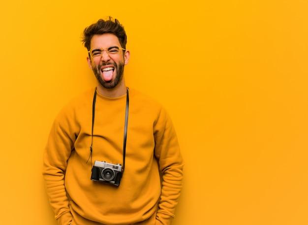 Giovane fotografo uomo divertente e amichevole che mostra la lingua