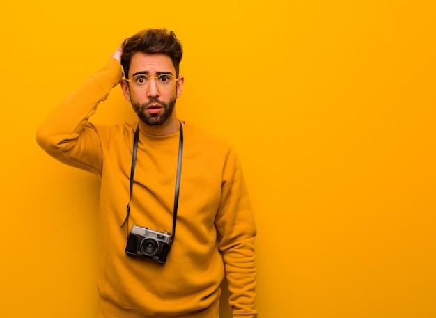 Giovane fotografo uomo preoccupato e sopraffatto