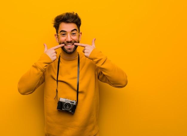 Giovane fotografo uomo sorride, indicando la bocca