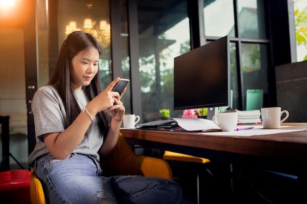 Giovane freelance asiatica con smart phone in mano che lavora in ufficio a casa