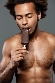 Giovane gelato mangiatore di uomini africano bello sopra la parete grigia.