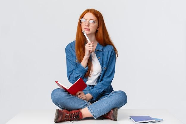 Giovane genio femminile concentrato, riflessivo e creativo con i capelli rossi, con gli occhiali, guardando perplesso e riflettendo sulla soluzione del compito, scrivendo i compiti seduto sul pavimento con taccuino e penna