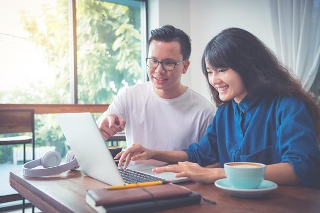 Giovane gente di affari asiatica che lavora con il computer portatile in caffetteria